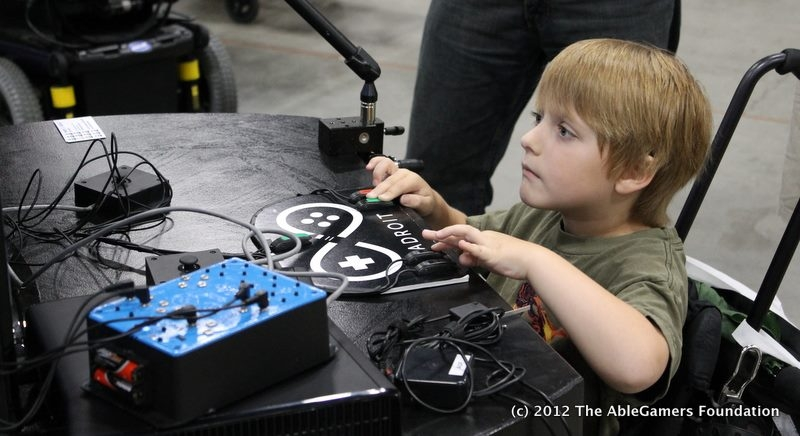 Child playing video games with assistive technology