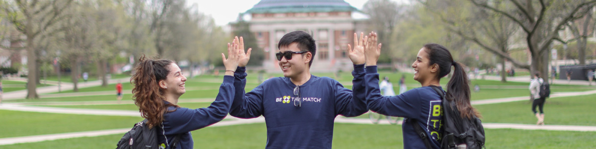 Photo of students on campus giving high fives