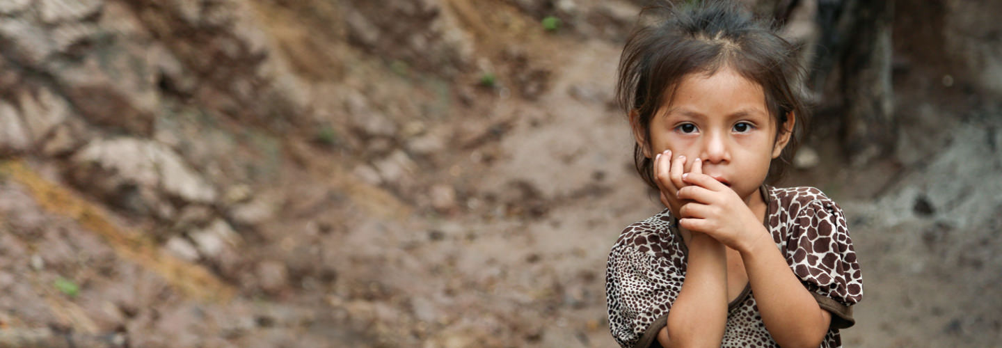Little girl stands in poverty. Your gift matched