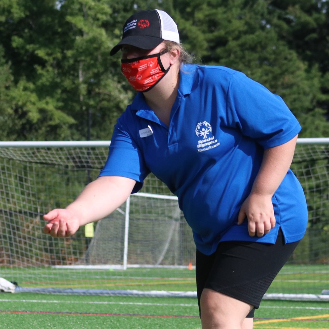 Female athlete playing corn hole with a face mask on.